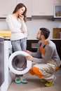 Workman and client near washing machine professional visiting customer for after sales service at home focus on man Royalty Free Stock Photos