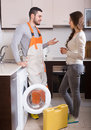 Workman and client near washing machine professional visiting female for after sales service at home Stock Photos