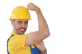 Workman flexing his muscles showing work force conceptual image of a strong young in a yellow industrial hardhat to show the power Royalty Free Stock Images