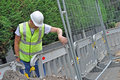 Workman looking down at fench in hi vis jacket and hard hat Royalty Free Stock Photo