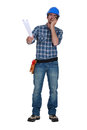 Workman with plans and a walkie talkie Stock Image