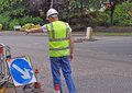 Workman pointing down toward road works in hi vis jacket and hard hat to Royalty Free Stock Photo