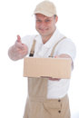 Workman pointing to a cardboard box that he is holding with thumbs up and broad smile of endorsement and approval Royalty Free Stock Image