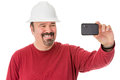 Workman posing for a self portrait with neat goatee beard weaning hardhat giving cheesy grin as he looks into the camera on Stock Photos