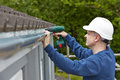Workman replacing guttering on exterior of house with drill Royalty Free Stock Images