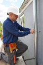 Workman replacing guttering on exterior of house repairing Royalty Free Stock Photo