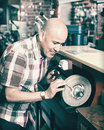 Workman resharpening knives on machine positive mature interlock spiral wheel system Stock Photography