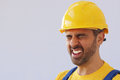 Workman screwing up his eyes in pain middle aged wearing a safety helmet or hardhat due to a migraine headache or injury over a Stock Image