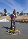 Workman smoothing newly poured concrete using helicopter machine on flooring at housing estate Royalty Free Stock Photo