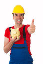 Workman with thumb up is showing a piggy bank Royalty Free Stock Image