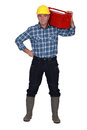 Workman with a tool box on his shoulders Stock Photo