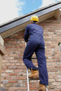 Workman up a ladder climbing to the roof Stock Image