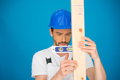Workman using a spirit level handsome young in hardhat holding it horizontally against plank of wood against blue background Royalty Free Stock Images