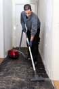 Workman vacuuming a passage during renovations after removing the old floor tiles Stock Image