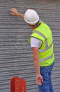 Workman working on metal roller door in hi vis jacket and hard hat Stock Photos