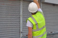 Workman working a on metal roller door in hi vis jacket and hard hat looking up at top of door Royalty Free Stock Images