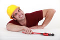 Workman with a wrench in tight spot Stock Photo