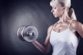Workout athletic woman doing with weights on dark background Royalty Free Stock Image