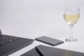 Workplace with black laptop computer, digital graphic tablet and pen smart phone and glass white wine on white background Royalty Free Stock Photo