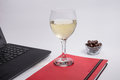 Workplace with black laptop computer, notebook, chocolate balls and glass white wine on white background Royalty Free Stock Photo
