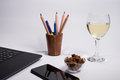 Workplace with black laptop computer, smart phone, box with color pens and pencils dry grapes and glass white wine on white backgr Royalty Free Stock Photo