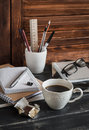 Workplace with business objects - books, notebooks, pens, tablet, glasses and a cup of coffee and chocolate. Royalty Free Stock Photo
