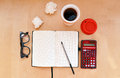 Workplace with open notebook glasses calculator and cup of coffee or tea on wooden desk creative red light Stock Photo