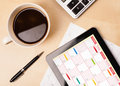 Workplace with tablet pc showing calendar and a cup of coffee on a wooden work table close up Stock Images