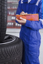 Workshop worker checking tires Royalty Free Stock Photo