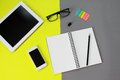 Workspace desk with tablet computer, blank notebook, pencil, eye glasses, smart phone, clip and paper note on yellow and gray back Royalty Free Stock Photo
