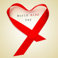 World aids day a red ribbon forming a heart and the text on a beige background Royalty Free Stock Photography