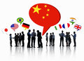 World business people having a group discussion silhouettes of with each other and speech bubbles with different national flags Royalty Free Stock Image