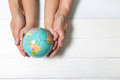 World concept: Two human hands holding global on wooden background. Royalty Free Stock Photo