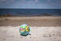World globe beach ball lying on beach by the ocean. Royalty Free Stock Photo
