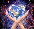 World in heart shape with over women human hands Royalty Free Stock Photo