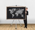 World map on blackboard businessman in tuxedo and Stock Photo