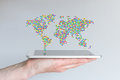 World map floating above a modern smart phone or tablet. Hand holding mobile device in front of grey background. Royalty Free Stock Photo