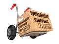 Worldwide shipping cardboard box on hand truck with slogan white background Royalty Free Stock Photos