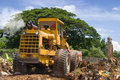 Worn bulldozer on tropical terrain Stock Photos
