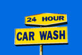 Worn car wash sign hour with blue sky background Stock Photo
