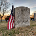 Worn Gravestone of a Military Veteran Honored with an American Flag Royalty Free Stock Photo
