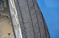 Worn tire of a blue car detail photo Royalty Free Stock Photo