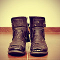 Worn and torn boots picture of a pair of on the floor with a retro effect Royalty Free Stock Photo