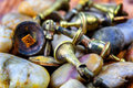 Wornout rusty brass cupboard handles or doorknobs in a pile on top of colourful pebbles Stock Photo