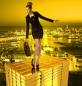 Worried business woman on gold tower and town with bag balancing with a in background Royalty Free Stock Images