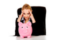 Worried business woman with a piggybank behind the desk Royalty Free Stock Photo