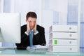Worried businessman looking at binders on desk Royalty Free Stock Photo