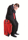 Worried businessman on luggage sitting red isolated white Royalty Free Stock Images