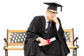 Worried college graduate sitting on bench and holding a diploma isolated white background Stock Photos