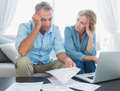 Worried couple using their laptop to pay their bills at home in the living room Royalty Free Stock Photos